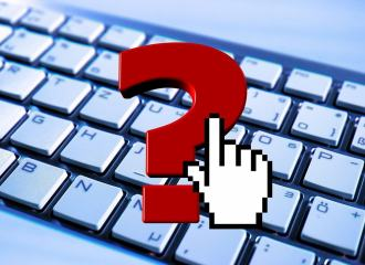 Question mark over a computer keyboard with a mouse curser over the question mark