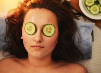 Woman laying on her back having a beauty spa treatment with sliced cucumbers over her eyes
